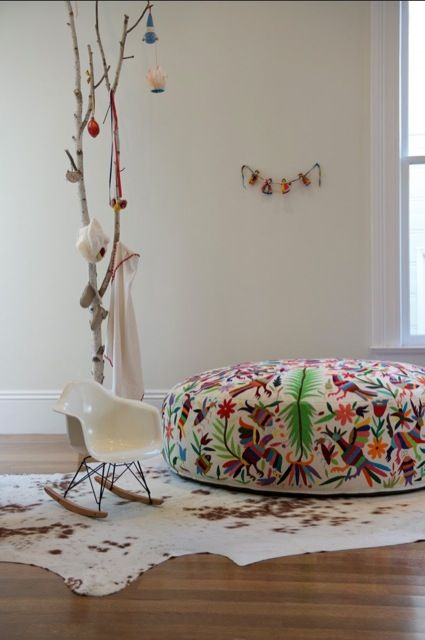 Branches as Children's Room Decor. Also love the large embroidered ottoman mixed with the cow hide and rocker. A room that could grow with any child.