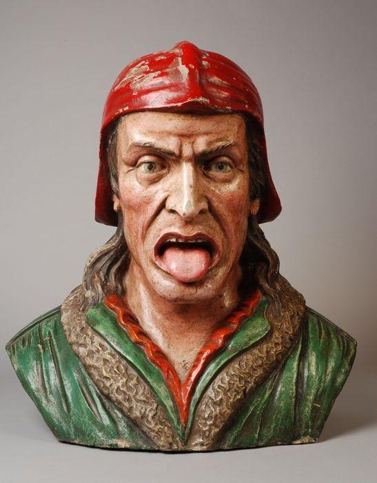 Gaper met rode muts, groene mantel met bontkraag, rood hemd en roze gezicht (Dante-type)
