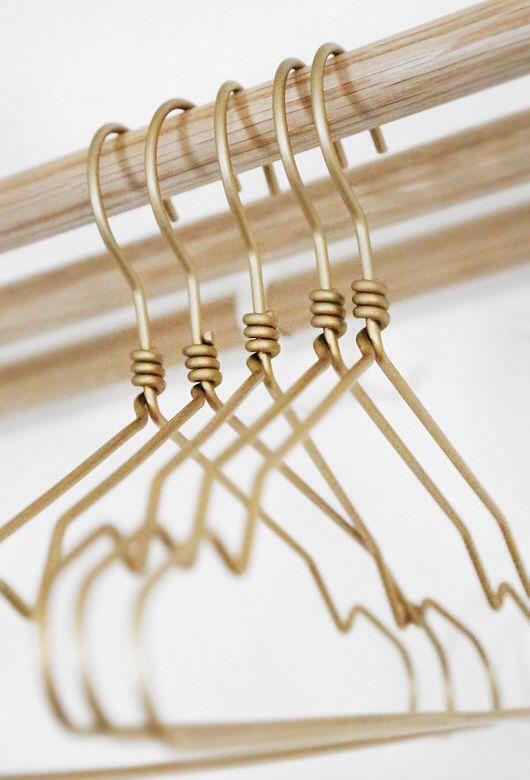 Gouden hangers voor de kleding die wordt geshowd in de winkel want dat past perfect bij de kledingrekken.