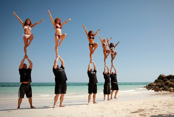The men of the Ravens cheerleader stunt team collaborate with the female cheerleaders on some moves on the beach.