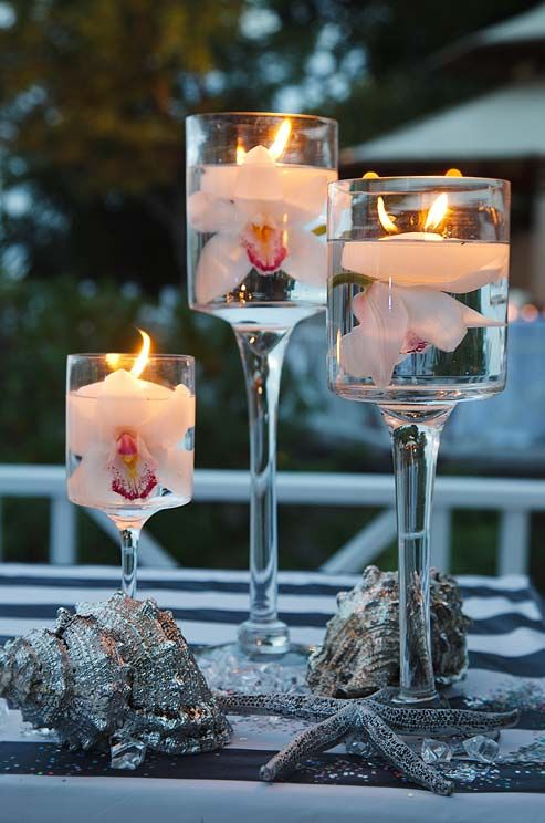 Cast a warm glow by topping single submerged Cymbidium orchids   with floating candles in holders of varying heights.