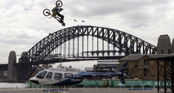 SHMCC member Travis Pastrana of the US flies over the spinning blades of a helicopter with the Sydney Harbour Bridge in the background.