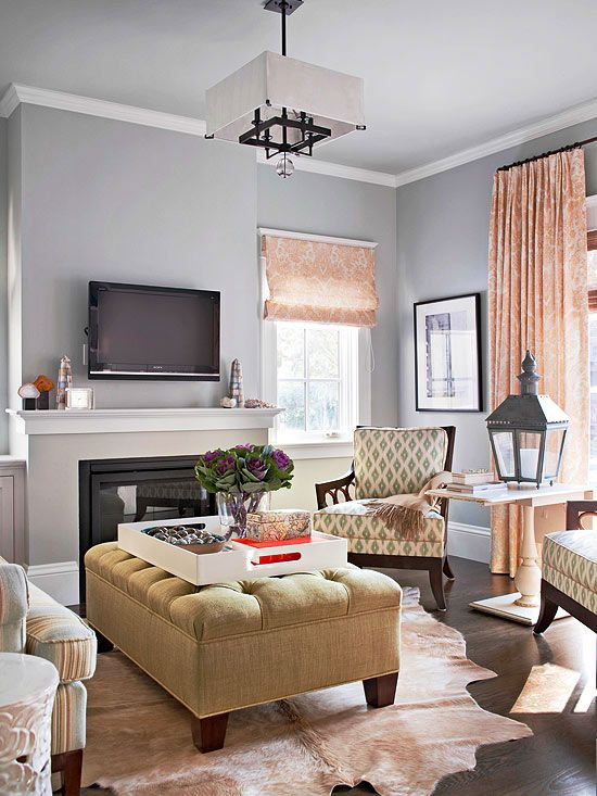 Wrap your walls in the calm embrace of gray-blue paint. Serenity serves as a modern neutral in this carefully curated living room, while pops of pink appear in surrounding window treatments. A cozy cowhide rug picks up the rose tones while tying into neutral furnishings./