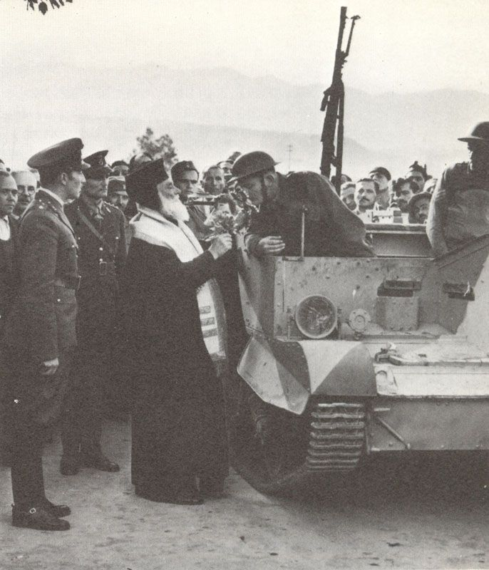 The Greek Orthodox Bishop of Canea (Crete) blesses British troops. In front is a Bren Gun carrier.