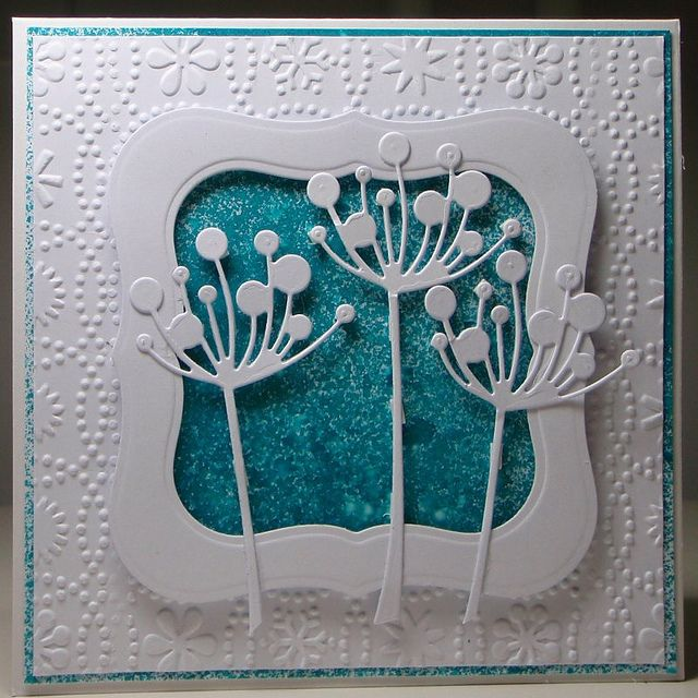 white card with die cut frame and flowers, embossing folder design on top layer and some wonderful shimmery blue stuff inside the frame behind the flowers...