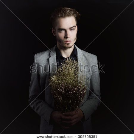 Portrait of attractive mysterious young man with dry flowers over black background.
