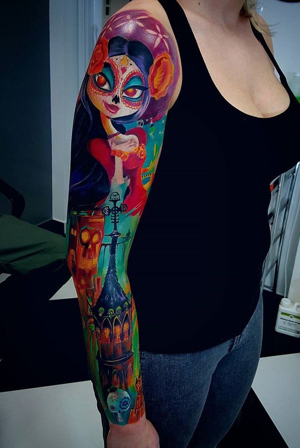 A brightly inked sleeve tattoo. What makes this design pop out is the usage of such bright and fun colors and color combination. Simply by looking at the tattoo you can already feel the energy coming from it.