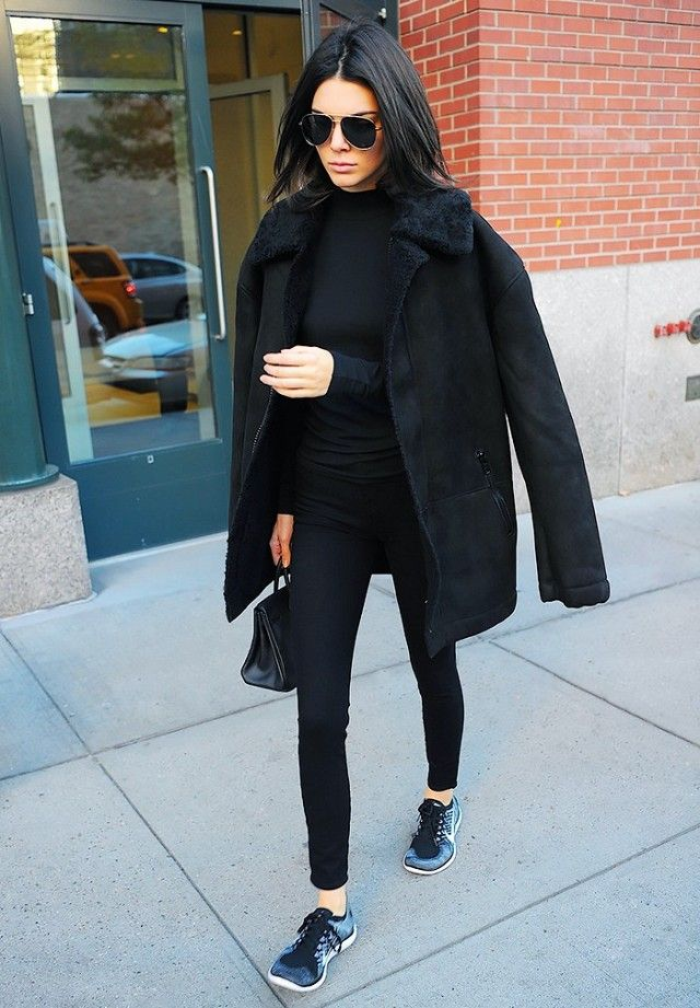 Kendall Jenner wears a black turtleneck with a Yeezy Season 1 oversized shearling coat, skinny jeans and Nike Free 4.0 Flyknit Running shoes.