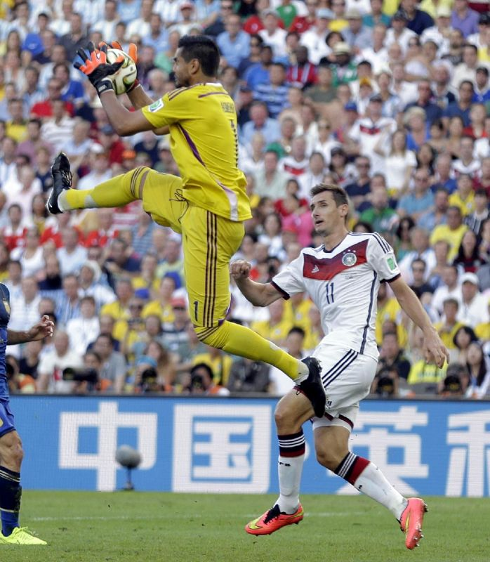 Argentina's goalkeeper Sergio Romero catches a loose ball in front of Germany's Miroslav Klose during the World Cup final soccer match between Germany and Argentina at the Maracana Stadium in Rio de Janeiro, Brazil, Sunday, July 13, 2014