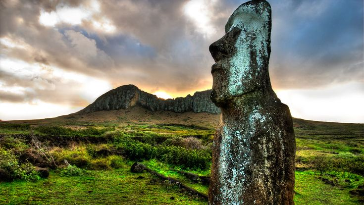 The sun sets behind a moai (stone statue) and Rano Raraku - the volcanic quarry where it once was carved.