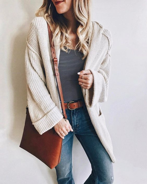 Striped tee, oversize knit cardigan sweater, skinny jeans, and tan leather bag & belt outfit