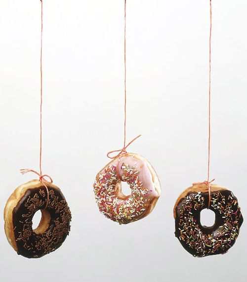 """Donut Chomp"" game: Thread donuts on a long piece of string and make sure to leave space between each. Have the kids race to eat the donuts off of the string with their hands behind their backs."