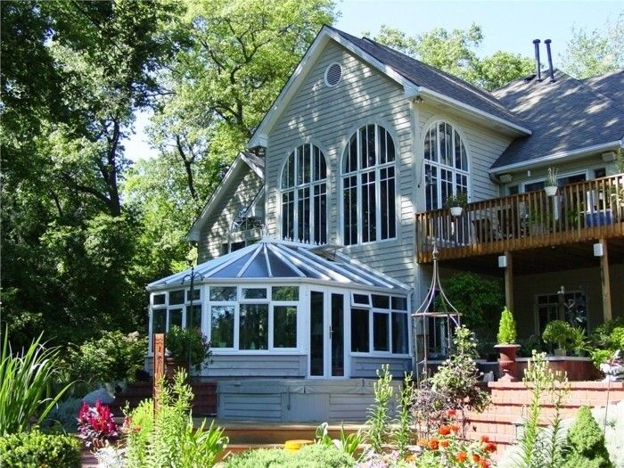 modele de veranda style victorien en harmonie avec le design et l'architecture de la maison adjacente, un formidable paysage forestier