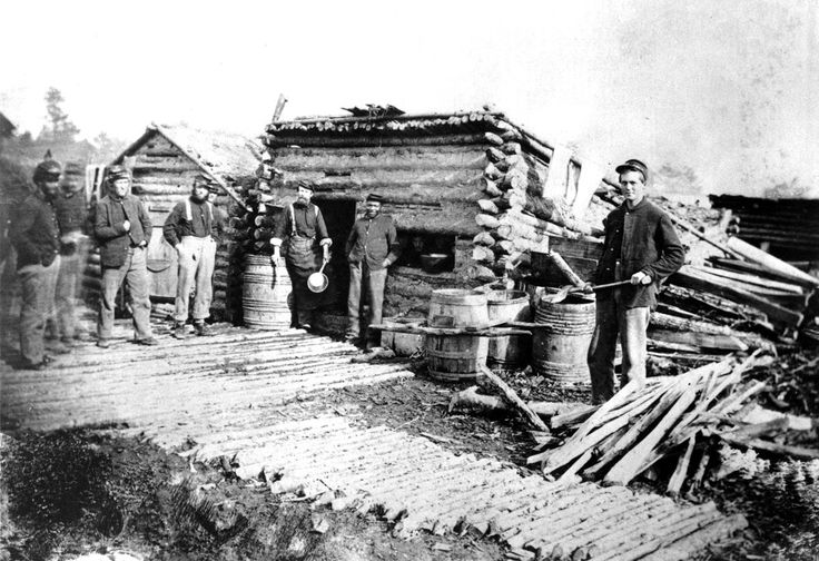 Serving as a soldier in uniform and getting regular army pay, a former slave (center, with hands in pockets) stands with other Federal soldiers at the Army of the Potomac winter headquarters near Fredericksburg, Virginia, The log hut served as a mess house for the regiment.