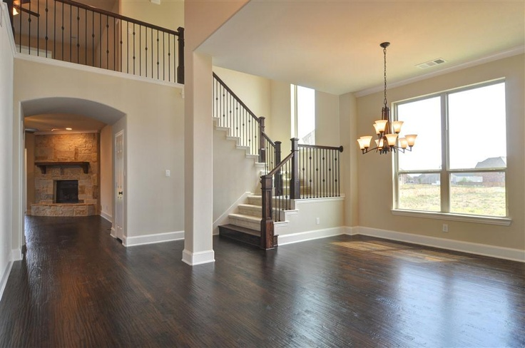 Nice view from front entry: Hand scraped wood floors, stone fireplace, picture-window in dining room, open stair case (would look better in wood).
