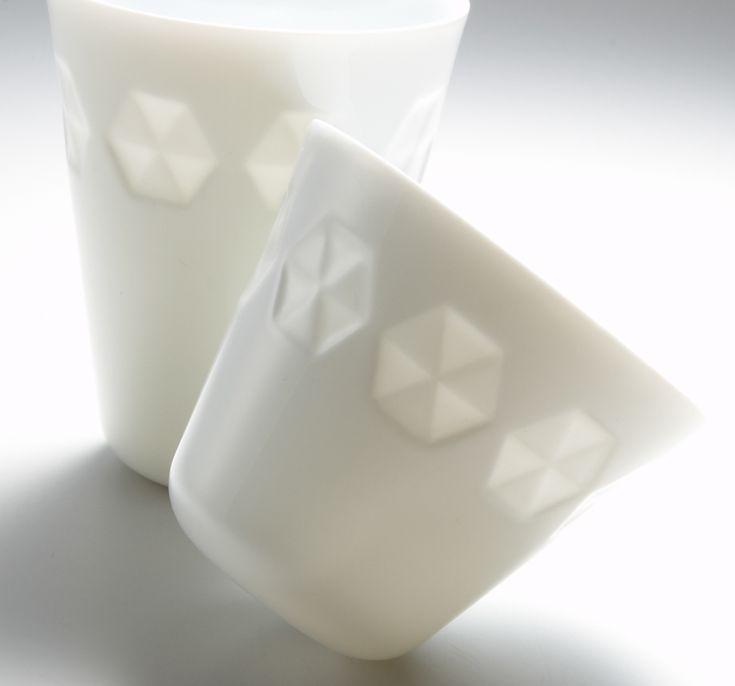 白磁にこだわり、現代の暮らしに合う「日本の白い器」を提案大正10年創業、品質とこだわりを大切に白い器を作り続けている小田陶器。今から10年ほど前、白磁の素地にどうしたら豊かな表情を付けられるか日々頭を悩ませていたところ、当時の営業担当がふと敷地内の建物の窓ガラスの表面に格子状の凹凸を発見。ガラスの厚い部分と薄い部分との光の透け方の違いに閃くものを感じ、デザイン室長の藤田広司さんにデザインとサンプル作成を提案。すぐに磁器土のカップに彫刻刀やカッターで彫模様を入れて試作品を焼いてみたそう。できあがりを光にかざすと、彫模様の部分が柔らかく透けて浮かび上がり……。「honoka」誕生の瞬間です。…
