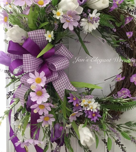A Breath of Spring time in Purple! A basket of smiles! Purple daisies, white daisies, purple and white tulips, cherry blossoms, and lots of leafy greenery are just bursting from this beautiful wreath. In the center, a large bow of purple and white gingham and a solid purple satin ribbon brings it all together. This beauty will grace your entrance and be the herald of spring at your home. Measuring from highest stem tip to the very lowest, it measures 30 inches and about 22 inches across. The…