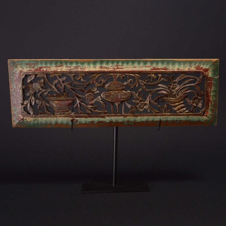 Inlaid wooden panel with residual coloration, part of a furniture decoration, probably of a canopy bed. It is equipped with an iron pedestal. Size: 35 x 12 cm.