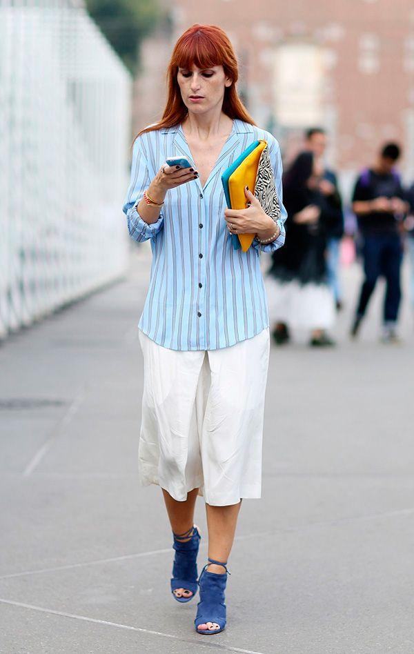 Street style look com camisa listrada, calça cropped, sapato azul e maxi clutch amarela.