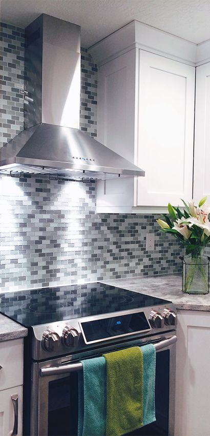 Beautiful Stainless Steel Wall Mount Range Hood from Proline Range Hoods. Classic White Kitchen with a gray toned tile backsplash featuring the Proline PLJW 129 Vent Hood sent to us from one of our customers. | View Our Range Hood Selection: http://prolinerangehoods.com