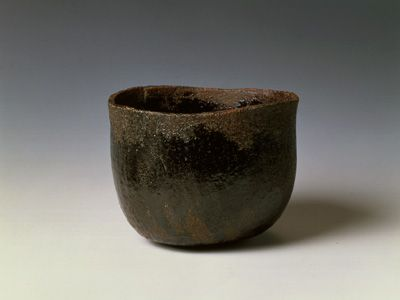 """RAKU WARE   Raku Museum-Collections:Hon'ami Kôetsu (1558 ~ 1637)  Black Raku tea bowl named """"Murakumo"""" The mouth is curved outward, the black glaze applied with deliberate irregularity around the mouth and the area of the body to show the red clay texture underneath. It is representative of Kôetsu's tea bowl."""
