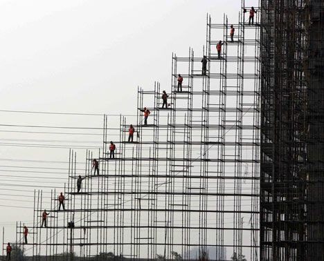 """Construction Greater Noida, India  Photographer: Kamal Krishore, New Dehli, India  Photographer's comment: """"The labourers line up from bottom to top to pass building materials. The picture looks like an artwork.""""  Judge's comment: """"This is construction at its most humorous. It made me smile. There is a real harmony between the people and a constant sense of backwards and forwards."""" Maxwell Hutchinson."""