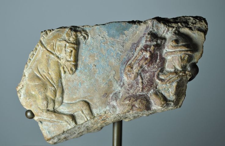 Greek terracotta relief  with two confronting horses and Alexander the Great, 2nd century B.C. Supposedly from Central Italy, Greek hellenistic terracotta palque, probably architectural decoration, with two confronting horses and horseman wearing Attic helmet with head turned back, considering this battle scene the horseman can be Alexander the Great with his horse Bucephalus, cobalt blu and red, unpublished for scene and for type, 16 cm long. Private collection