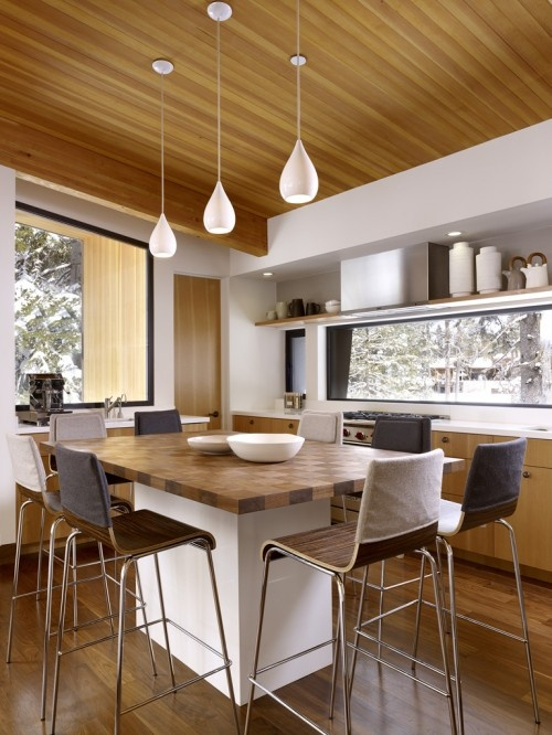 While we might not usually associate a kitchen full of clean modern lines with coziness, this kitchen is a perfect spot to warm up with some cocoa after a day of playing in the snow. Even the barstools are wearing snuggly cozies.