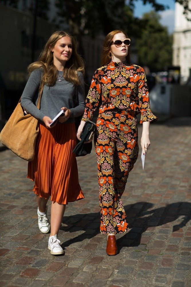 Street Style na London Fashion Week: copper midi-skirt paired with a blue blouse and an ocher shopper. The second outfit features a jumpsuit in fall colors