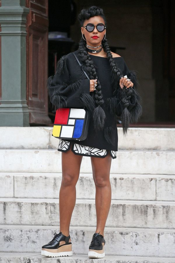 Janelle Monae in a black sweatshirt, abstract print mini-skirt, creepers, and a color-block statement crossbody bag.