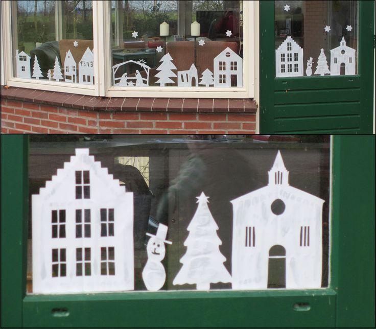 Knippen van papieren huisjes, kerken, kerstbomen, sterren, sneeuwpoppen etc. Met behanglijm opplakken op het raam.