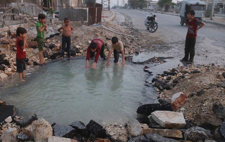 Estos niños sirios usan como piscina el cráter que dejó la explosión de una bomba sobre su ciudad