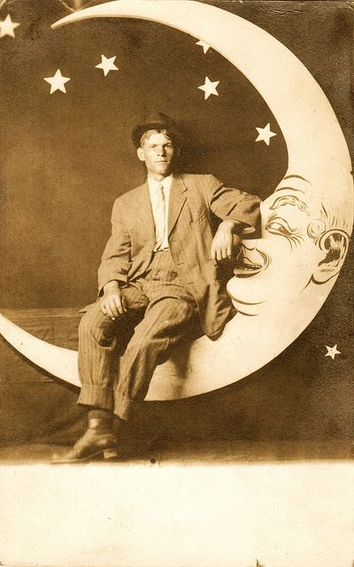 Young man sitting on paper moon, circa 1910
