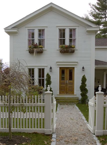 Okay, a white picket fence is mandatory...  Love the natural wood door with an all white house.