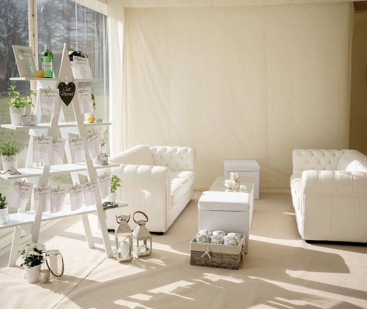White Chesterfield Sofas and White Fabric Cubes and Coffee Tables for an all-white wedding chill out area.