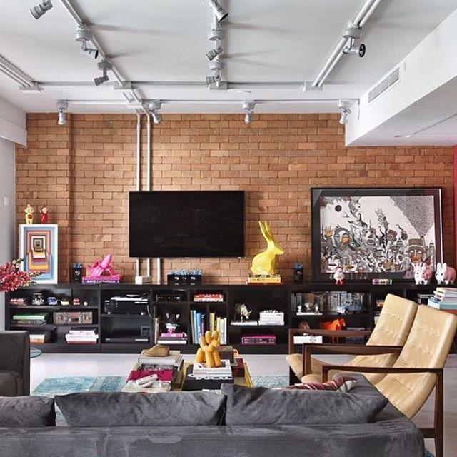 Com estilo industrial, a sala deste loft é linda e bemcontemporânea. e atual essa decoração! As poltronas levam a assinatura do designer fic Jader Almeida. Parede de tijolo de demolição.