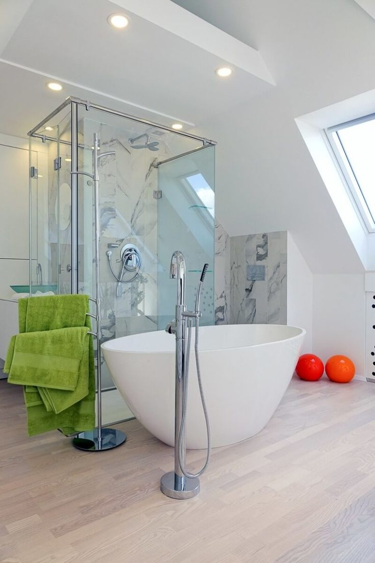 A bathtub in a bedroom is a hot decor trend, this area is clad with marble inspired tiles