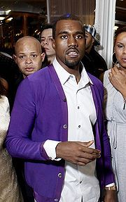 Kanye wearing a purple cardigan with a white shirt, this is unlike what the average man would wear, showing how Kanye isn't like most men.