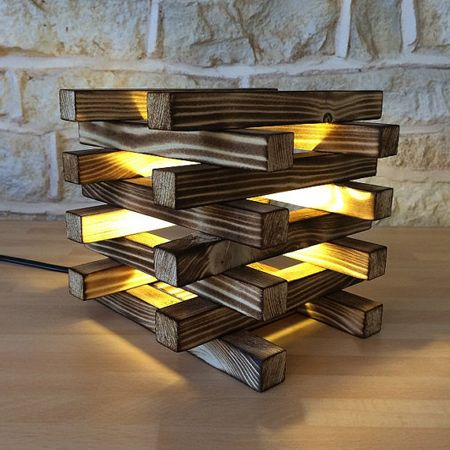 Burnt wood and small wood blocks combine to create a stunning table lamp design. The gaps between each piece of wood lets the light flow in all directions