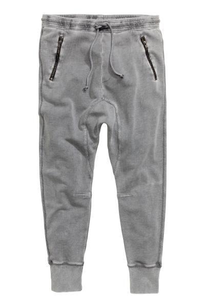 Trainingsbroek: Een broek van joggingstof met een laag kruis en smal toelopende pijpen met een boord onderaan. De broek heeft elastiek en een trekkoord in de taille, steekzakken met ritssluiting en een achterzak.