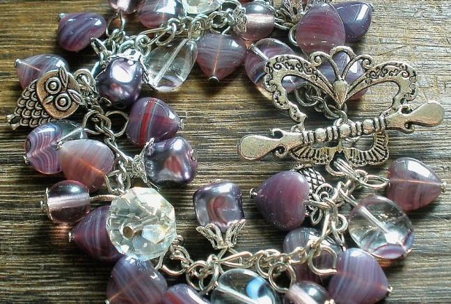 Bohatý náramok so srdiečkami v žíhanom slivkovom odtieni. Nájsť v náramku môžte rôzne korálky -žíhane fialovo-biele, guľlky, veľké brúsené donuty dodávajú na luxusnosti, atypické perly s filigránovými kaplíkmi , kovový prívesok sovy a veľký výrazný motýľ, kt. je zároveň aj zapínaním