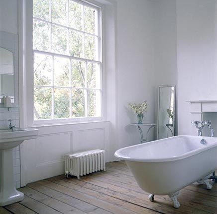Inrichting van een badkamer in een Victoriaans huis in Londen. Het raamkozijn is prachtig en de badkamer heeft veel authentieke details