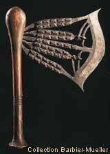 Hache_kilonda_songye - En République Démocratique du Congo, fabriquée par les forgerons Songye et Nsapo, cette arme de prestige est une hache Kilonda.  Elle comporte 92 petites têtes qui ornent les axes. Plus rarement, des figurines en fer ou en cuivre étaient insérées dans le décor :