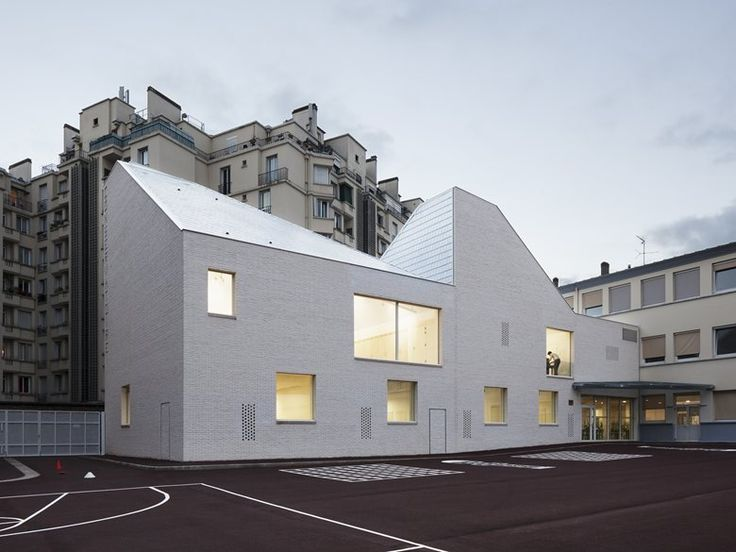 The project is located at the heart of a city block in a school playground. The new volume extends an existing school building up the slope of the passageway that leads onto the site, and settles itself onto the playground's sloping surface....