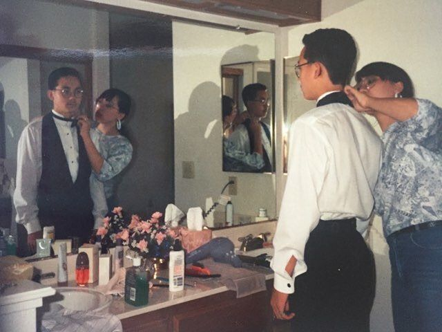 """Is that an Obsession perfume I see on the counter?  Names: Travis Yamaguchi and Akemi Yamaguchi  Location: Antinoch, CA Year: 1993 or 1994? Notes: """"I was in our parents bathroom helping my brother get ready for prom when my mom snuck this shot - I've always kinda liked how it captured two reflections and three angles.""""-Akemi  Insta: @imekasf —Guadalupe Rosales (of @veteranas_and_rucas And @map_pointz) #LACMAInstaResidency"""