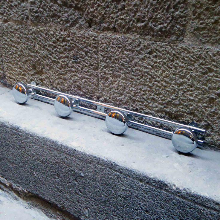 Perchero de pared de la década de los 70. Realizado en metal cromado con cuatro colgadores en forma de bola plana. Tiene dos agujeros para fijarlo a la pared facilmente. Medidas: L59 cms. En buen muy buen estado vintage.