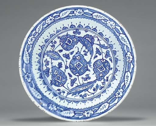 AN IZNIK BLUE AND WHITE POTTERY DISH  OTTOMAN TURKEY, CIRCA 1600  With sloping rim on short foot, the white interior painted in two shades of cobalt-blue with a swirling design of plants issuing saz leaves and three stylized pomegranates, the cavetto with a series of lobed motifs, the rim with alternating saz leaves and flowerheads on blue ground, the exterior with alternating floral spray and flowerheads,   13¼in. (34.2cm.) diam.