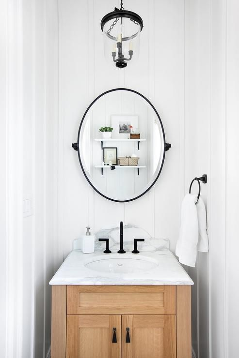 Small cottage powder room features walls clad in b…