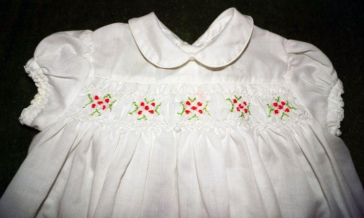 Algodón blanco infantil niñas smocked vestido con etiqueta de Polly Flinders. Esta fue la primera etiqueta de la década y este vestido es un ejemplo perfecto. Crujiente blanco y limpio con diminuto hilo cuello Peter Pan, hilo fruncido del pecho con bordados verde rojo y menta. Puffed manga corta tiene encaje trim. Dos botones yugo trasero. Sin manchas, sin puntos en condición prístina. 8 1/2 a través de los hombros 8 1/2 en el pecho del vestido acostado 8 1/2 a través de la es...