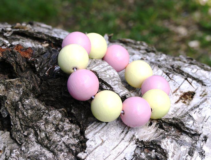 Náramek+z+dřevěných+korálů:+Žluto-růžové+Pastelový+náramek+z+dřevěných+korálů.+Korále+jsou+lehké,+nabarvené+akrylovou+barvou+a+pečlivě+přelakované+lesklým+lakem.+Jsou+vždy+navlčeny+na+pružnou+gumičku,takže+se+pohodlně+navlékají+na+ruku.+Velikost+a+počty+korálků:+11x18mm.+Každý+náramek+je+ruční+výroba+a+je+originál.+Na+některých+korálcích...